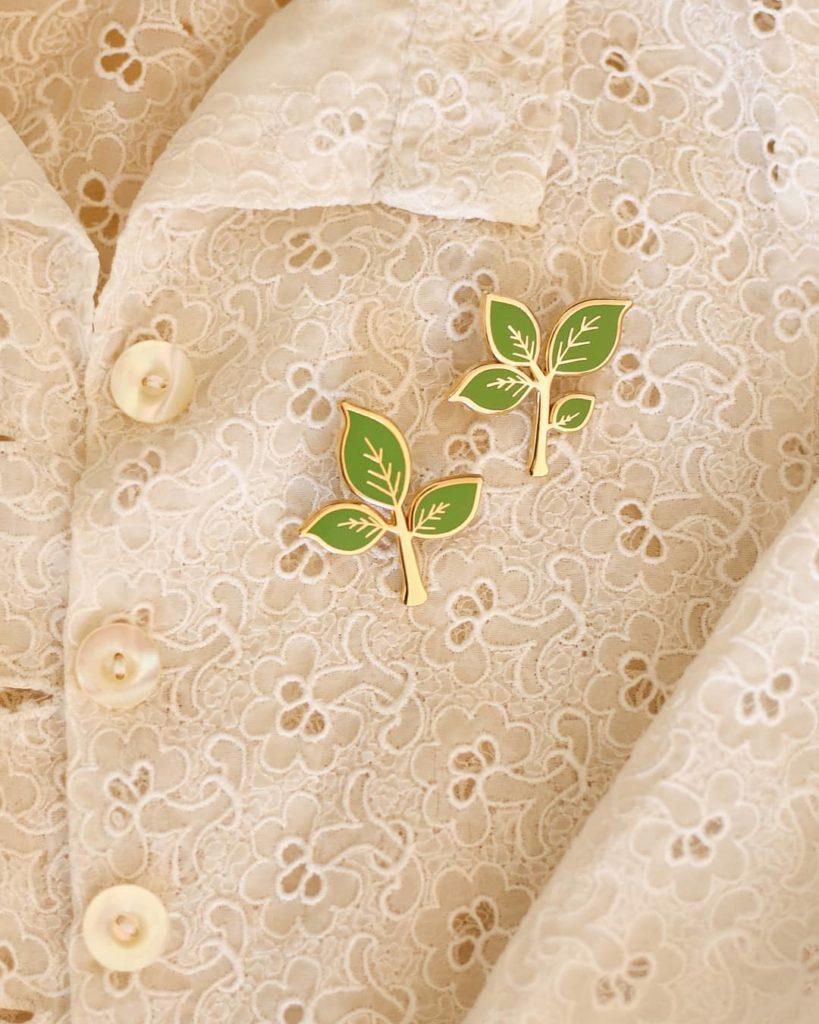 Deux pin's en forme de feuille sur une chemise en dentelle